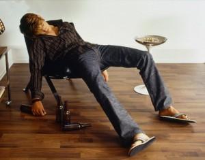 Drunken Young Man Sleeping in Chair Beside Beer Bottles